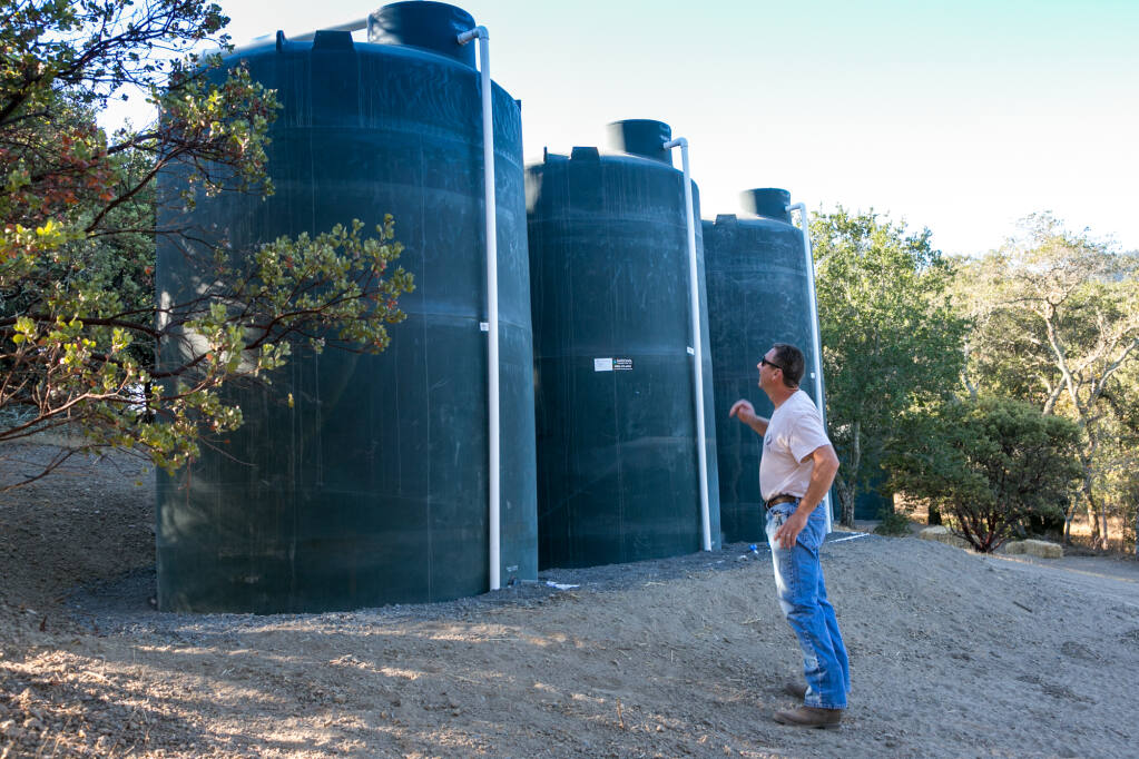 Steve Lee on his Glen Ellen property with three of the 5,000 gallon tanks designed to capture and hold rainwater, Wednesday, Oct. 14, 2020. (Photo by Julie Vader/special to the Index-Tribune)