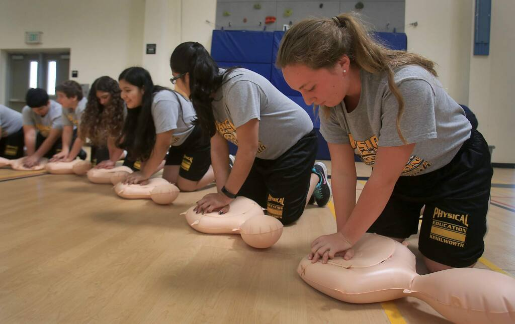 Megan Johnson, right, joins her classmates in a CPR instruction that was put on by the Petaluma Fire Department, Thursday March 30, 2017 at Kenilworth Jr. High in Petaluma. (Kent Porter / The Press Democrat) 2017