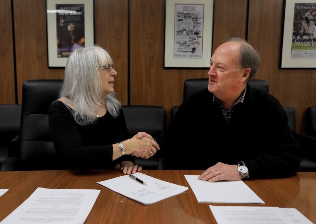 Sonoma County Gazette publisher Vesta Copestakes, left, and Sonoma Media Investments CEO Steve Falk, finalize the sale of the Gazette to SMI, Friday, Dec. 27, 2019 at the Santa Rosa Press Democrat in Santa Rosa. (Kent Porter / The Press Democrat) 2019