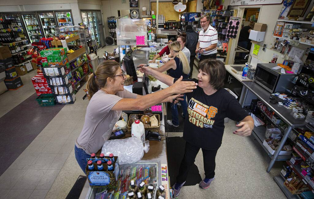 Annie Licardo, left, greets longtime customer Johanna Kolberg at Dave's Market on Third Street and Dutton Avenue in Santa Rosa. The market stayed open in the evacuation zone to serve local customers. (John Burgess/The Press Democrat)