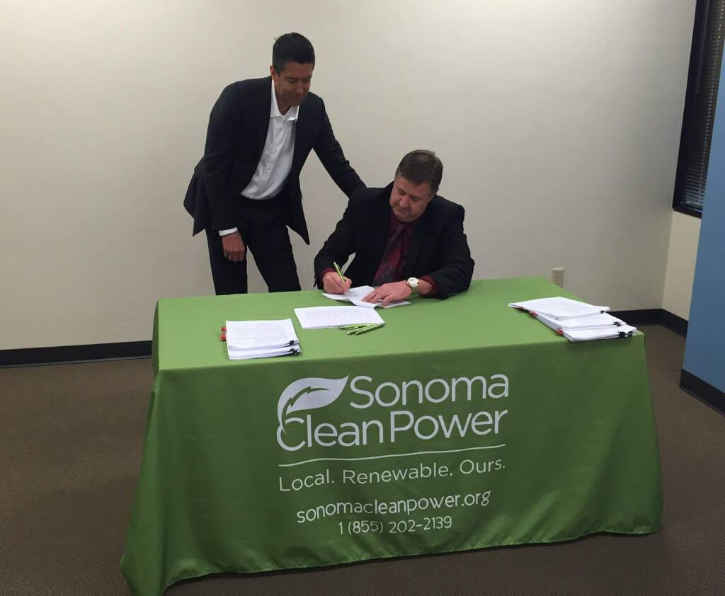David Cook (seated), chairman of Sonoma Clean Power's Procurement Ad Hoc Committee, and Pristine Sun CEO Troy Helming sign a contract for floating solar arrays on Feb. 26, 2015. (Sonoma Clean Power)
