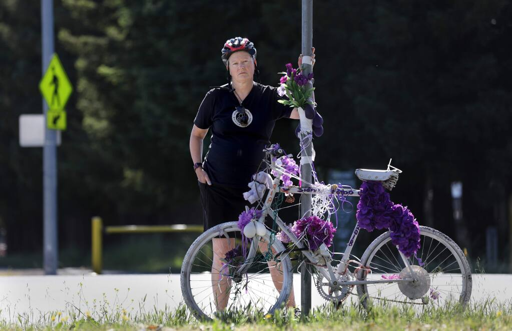 Eris Weaver, the Executive Director of the Sonoma County Bicycle Coalition, stands next to a 'ghost bike' memorial for the late Sidney Falbo on Stony Point Rd at the intersection of Hwy 12 and the Joe Rodota Trail in Santa Rosa on Friday, June 7, 2019. (BETH SCHLANKER/ The Press Democrat)