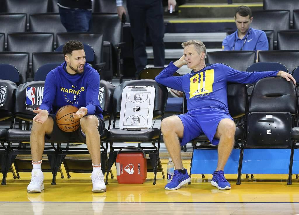 Kerr, who tore his ACL in college, believes Thompson, left, will be on the same recovery timeline as other players who sustained the same injury, and that means at least 11 months to a year. (Christopher Chung / The Press Democrat)