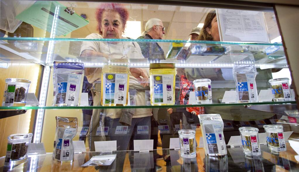 Judy Hess looks at a wide variety of cannabis products on the first day legal recreational marijuana sales in Sonoma County at SPARC/Peace in Medicine in Sebastopol on Jan. 1, 2018. (photo by John Burgess/The Press Democrat)