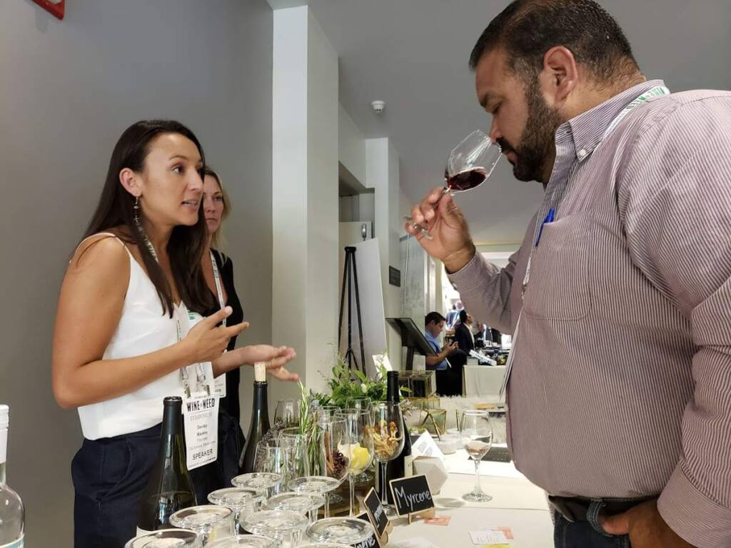 Devika Maskey, founder and CEO of TSO Sonoma speaks to an attendee sampling wine at the North Coast Wine & Weed Symposium on Aug. 2 in Santa Rosa. (Heather Irwin / The Press Democrat)
