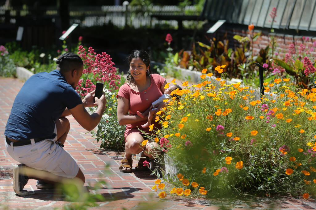 Peter Scott takes a photo of Sarahi Torres and their 1-month-old son Onyx Scott-Torres at Luther Burbank Home and Gardens in Santa Rosa, California on Sunday, May 2, 2021. (Beth Schlanker/ The Press Democrat)