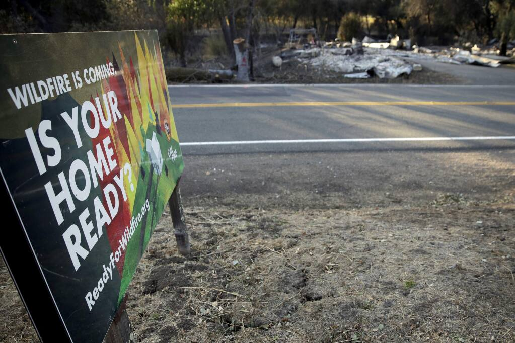 A sign, untouched by fire, stands across the road from a burned-out home that was destroyed by the Kincade Fire near Geyserville, Calif., Thursday, Oct. 31, 2019. The fire started last week near the town of Geyserville in Sonoma County north of San Francisco. (AP Photo/Charlie Riedel)