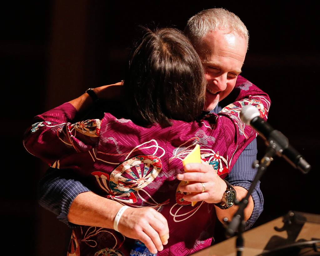 Santa Rosa firefighter Tony Niel embraces Sonoma State University president Judy Sakaki after they shared their stories from the night of the Tubbs Fire during Thicker Than Smoke, an evening of community storytelling at Sonoma State University's Weill Hall in Rohnert Park, California, on Friday, August 3, 2018. (Alvin Jornada / The Press Democrat)