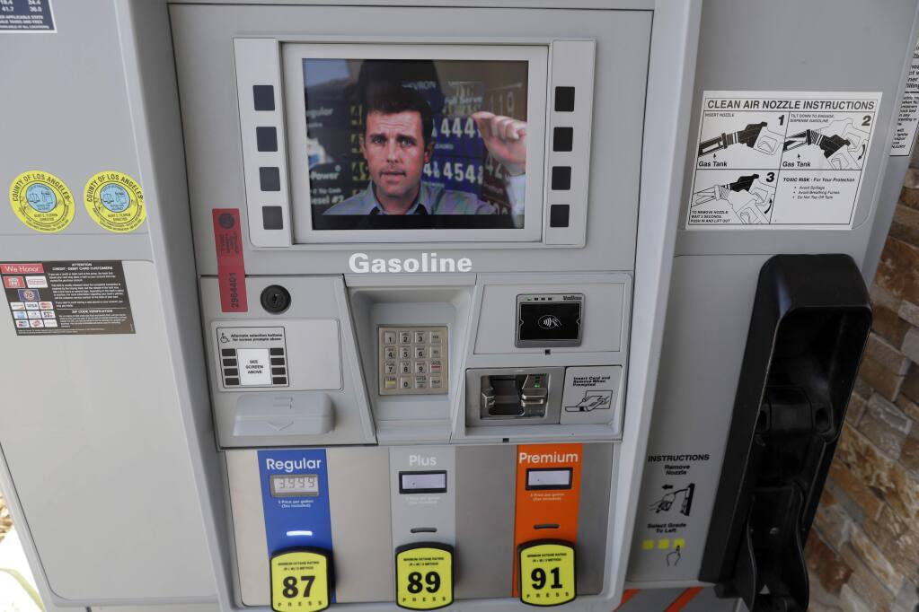 An ad supporting Proposition 6 plays on a screen on a pump at a gas station Wednesday, Oct. 24, 2018, in Santa Clarita, Calif. The ads are part of an advertising blitz by Proposition 6 supporters trying to drive home a message to voters to overcome what they see as a misleading title and summary on the ballot. The feud over messaging comes just weeks before an election where Californians will vote in a series of contentious races for Congress and state offices and ballot measures including the proposal to repeal an increase in gasolines taxes and vehicle fees slated to fund $5 billion in transportation projects a year. (AP Photo/Marcio Jose Sanchez)