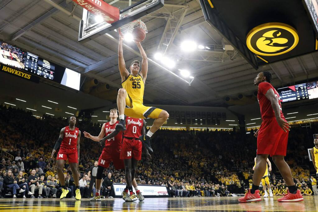 FILE - In this Feb. 8, 2020, file photo, Iowa center Luka Garza (55) dunks the ball during the second half of an NCAA college basketball game against Nebraska, in Iowa City, Iowa. Garza was selected to The Associated Press All-America first team, Friday, March 20, 2020. (AP Photo/Charlie Neibergall, File)