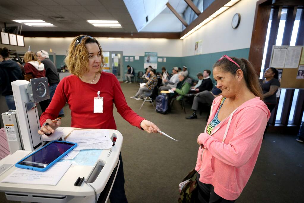 Motor vehicle representative Anya Hawkins, left, helps Nancy Reynaga figure out where to go to get a new ID at the Department of Motor Vehicles in Santa Rosa on Tuesday, January 7, 2020. (BETH SCHLANKER/ The Press Democrat)