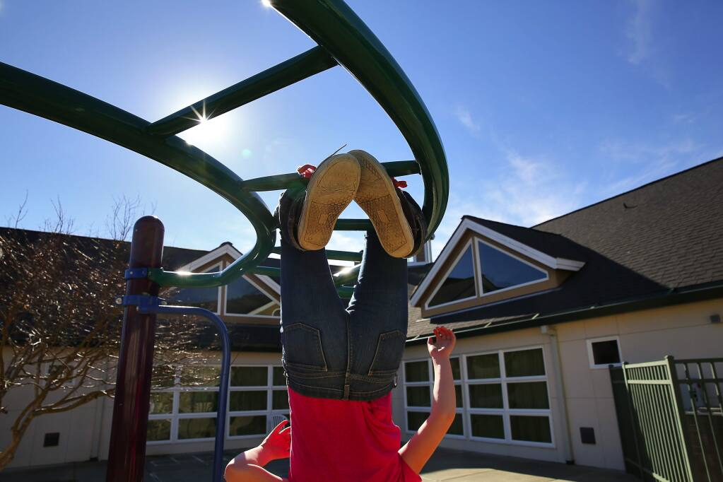 A young girl hangs upside down on a play structure at Valley of the Moon Children's Home in Santa Rosa on Tuesday, Feb. 14, 2017. (CHRISTOPHER CHUNG/ PD)