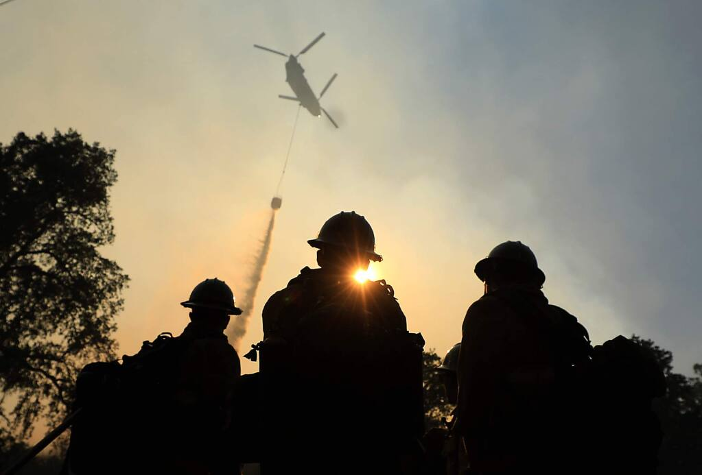 Ventura County firefighters watch as a helicopter makes a drop on a hot spot of the River fire in Scotts Valley near Lakeport, Friday, August 3, 2018. (Kent Porter / The Press Democrat) 2018