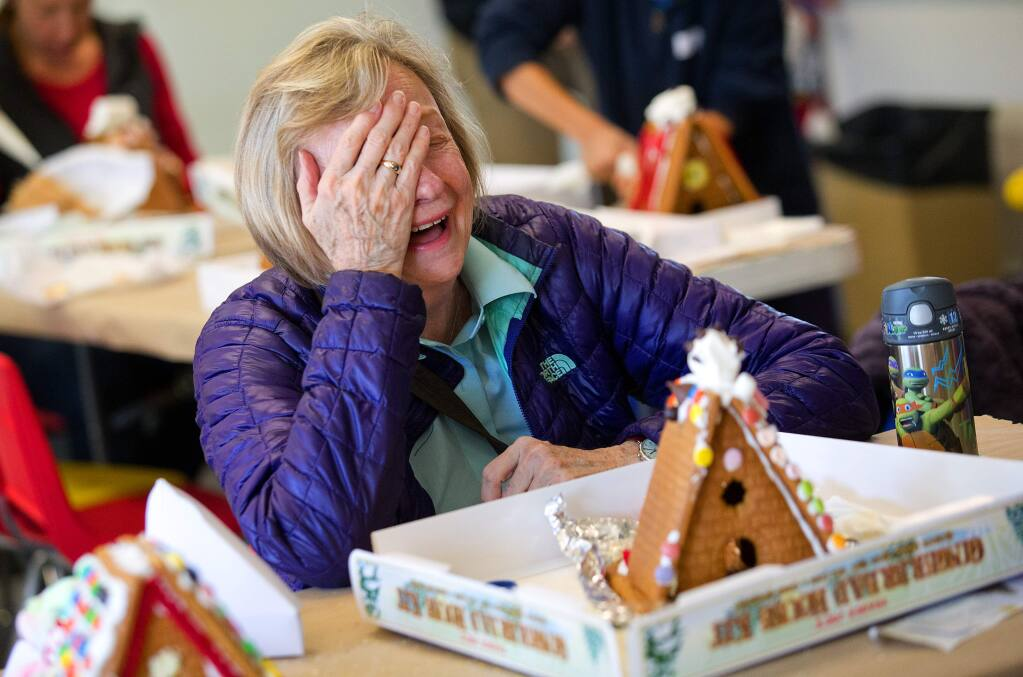 Children and their parents used M&M's, Fruit Loops, dummies, and plenty of licorice to create their own Snoopy's doghouse out of gingerbread complete with a marshmallow Snoopy on top on Saturday at the Charles M. Schulz Museum on Saturday. (photo by John Burgess/The Press Democrat)