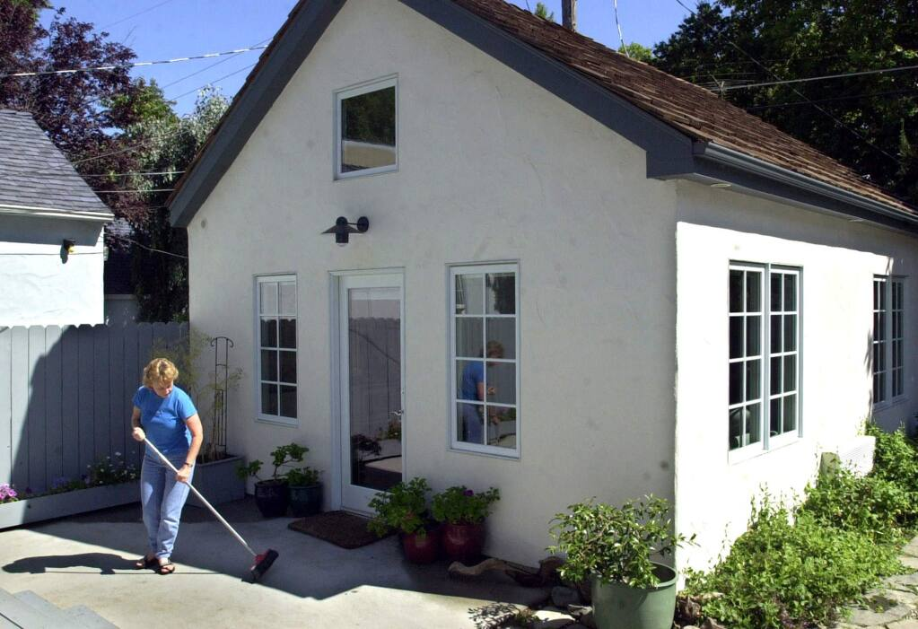 Christine Minnehan sweeps up in front of the granny flat in the backyard of her Sacramento home. (RICH PEDRONCELLI / Associated Press, 2002)