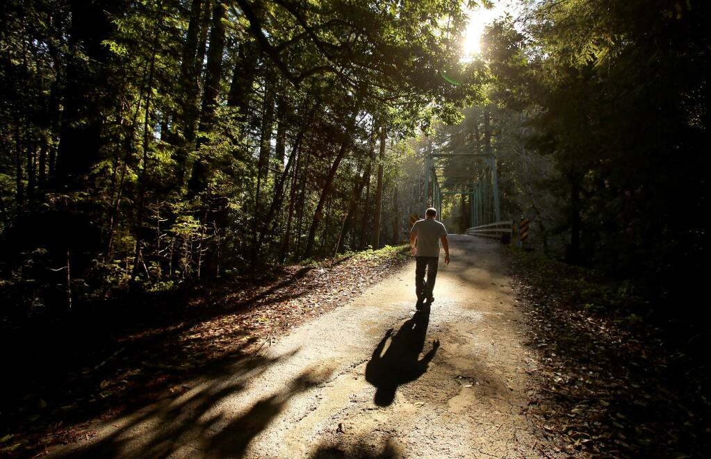 Mark Hancock, a publicity coordinator at Gualala Arts, walks along Gualala River Road, near the north fork of the Gualala River, in this November 2014 file photo. Nearly 30,000 acres of property are being sold by Gualala Redwoods, Inc.(Christopher Chung/ The Press Democrat)