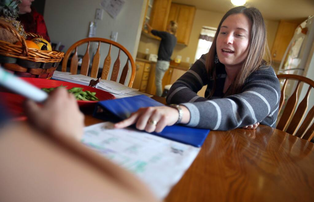 Former program director Emily Mann helps a child in foster care with a word search at Sonoma County Children's Village in Santa Rosa in February 2014. (Christopher Chung/ The Press Democrat)