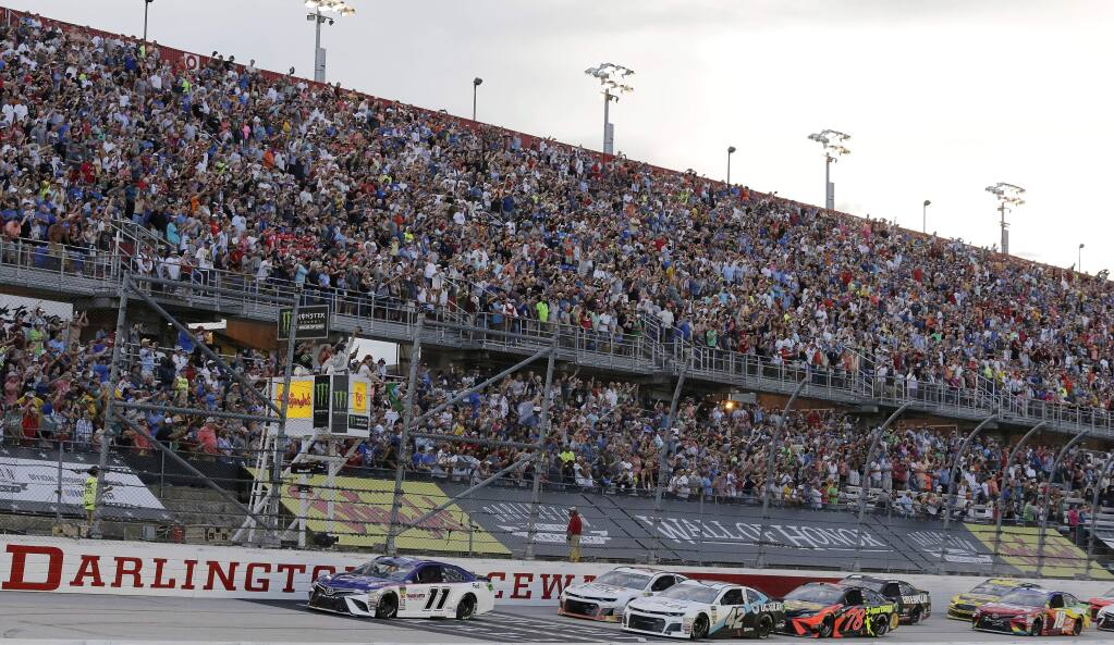 FLE - In this Sept. 2, 2018, file photo, Denny Hamlin (11) leads the pack to start the NASCAR Cup Series auto race at Darlington Raceway in Darlington, S.C. NASCAR will get its season back on track starting May 17 at Darlington Raceway in South Carolina without spectators, and the premier Cup Series plans to race four times in 10 days at a pair of iconic tracks. The revised schedule released Thursday, April 30, 2020, goes only through May and has a pair of Wednesday races - fulfilling fans longtime plea for midweek events. (AP Photo/Terry Renna, File)
