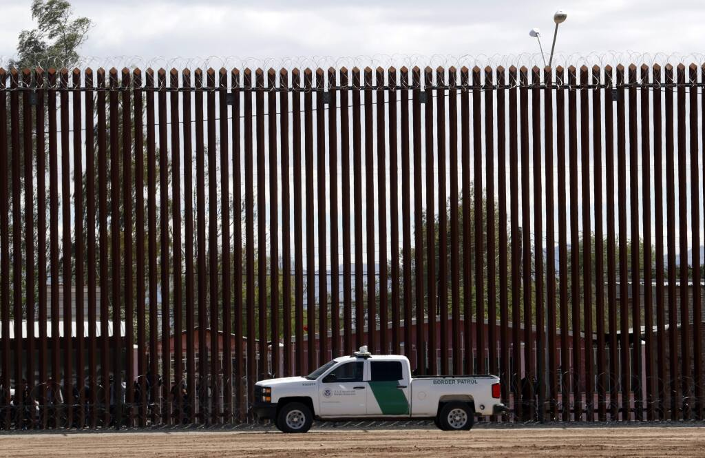FILE - In this April 5, 2019, file photo, a U.S. Customs and Border Protection vehicle sits near the wall as President Donald Trump visits a new section of the border wall with Mexico in El Centro, Calif. (AP Photo/Jacquelyn Martin, File)