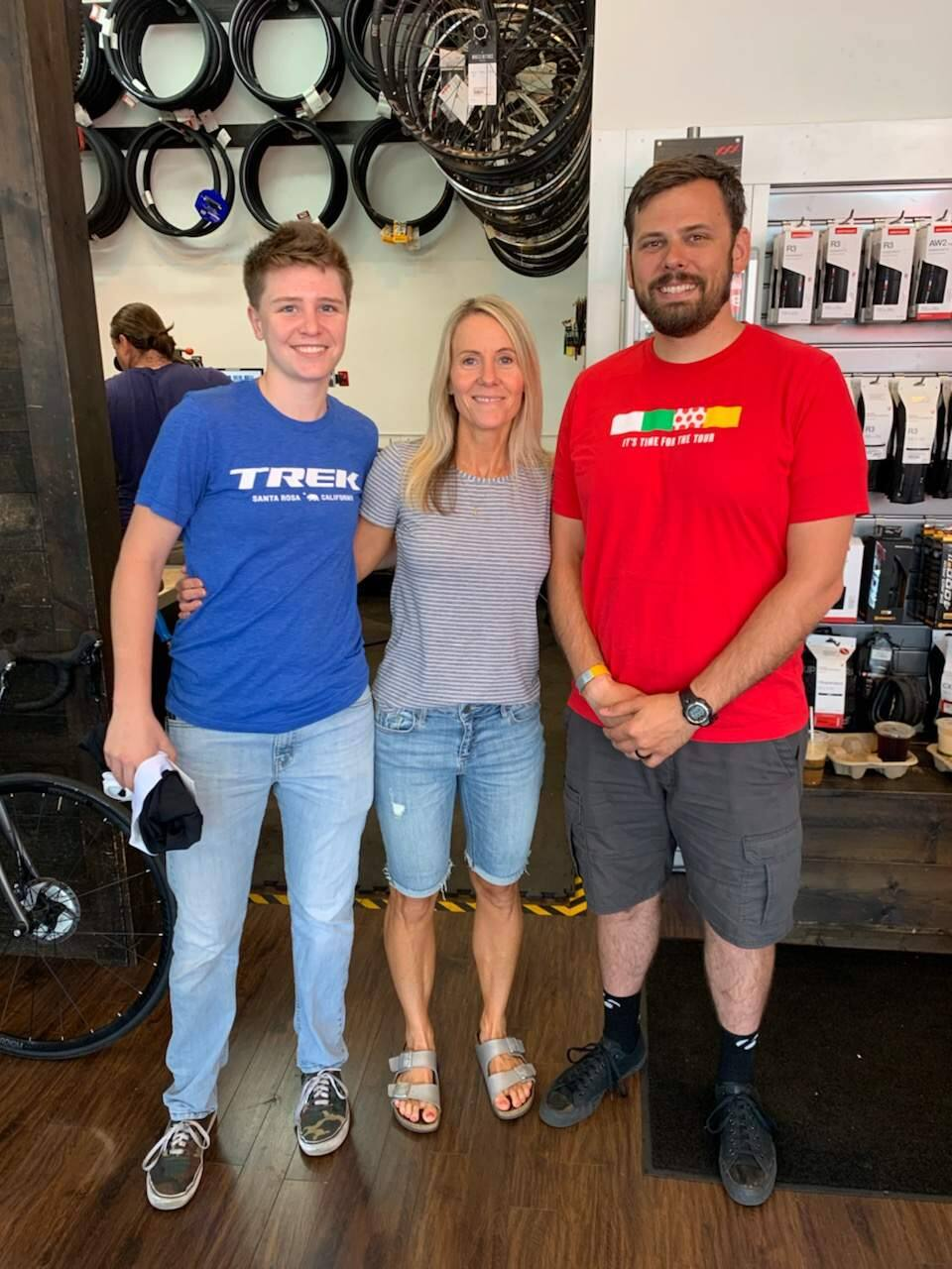 Marisa Denison, center, poses Saturday between Brianna Peebles, left, and Matt Roark of the Trek Bicycle store in Santa Rosa. Denison earlier finished the Ironman 70.3 Santa Rosa with the help of a bike gifted to her by the Trek store after a thief stole the bicycle she intended to ride. (Courtesy of Marisa Denison)