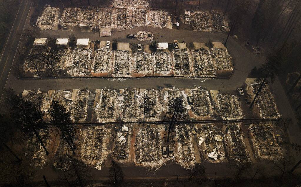 FILE - This Nov. 15, 2018, aerial file photo, shows the remains of residences leveled by the Camp Fire in Paradise, Calif. A federal bankruptcy court judge on Wednesday, Nov. 27, 2019, rejected Pacific Gas & Electric's latest attempt to change a California law requiring utilities to pay for the devastation from wildfires ignited by their electrical equipment. The decision issued by U.S. Bankruptcy Judge Dennis Montali preserves a long-standing principle known as 'inverse condemnation.' (AP Photo/Noah Berger, File)