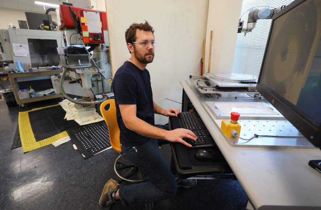Electrical engineer Orion Leland works with a peck and place robot moving thin film optics at Alluxa, in Santa Rosa on Thursday, March 19, 2020. (Christopher Chung/ The Press Democrat)