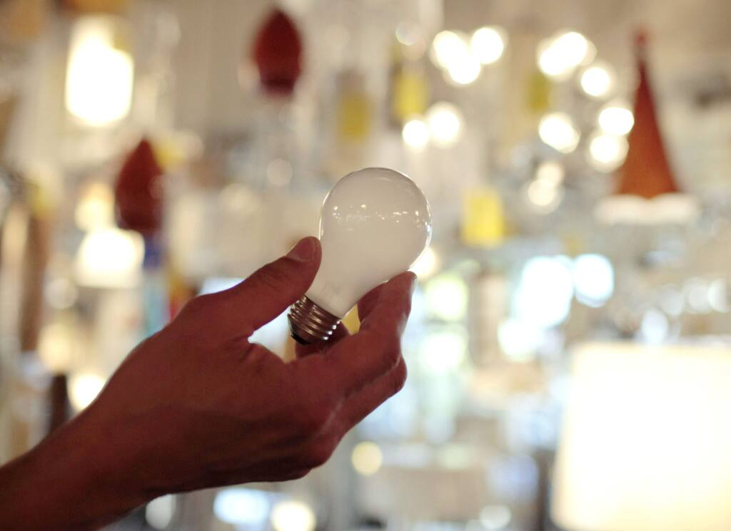 FILE - In this Jan. 21, 2011, file photo, Manager Nick Reynoza holds a 100-watt incandescent light bulb at Royal Lighting in Los Angeles. (AP Photo/Jae C. Hong, File)