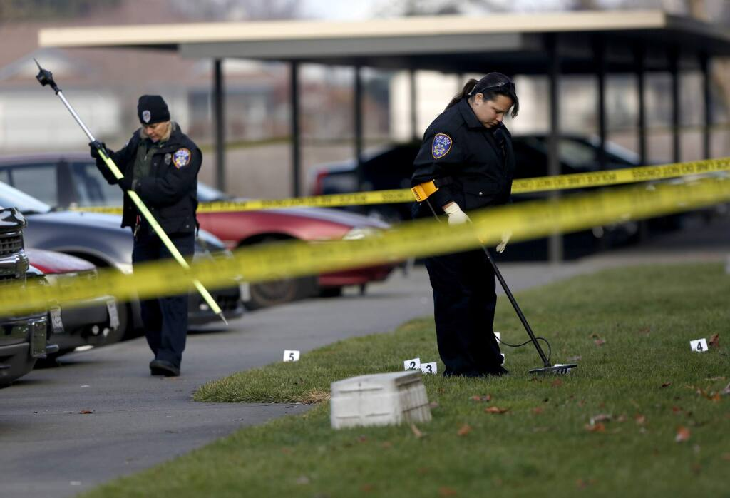 Santa Rosa Police field evidence technicians Adria Cooper, right, and Kristina Capeheart search for evidence as they investigate a fatal shooting that occurred in the early morning at Redwood Park Apartments in Santa Rosa, California on Tuesday, December 31, 2013. (BETH SCHLANKER/ The Press Democrat)