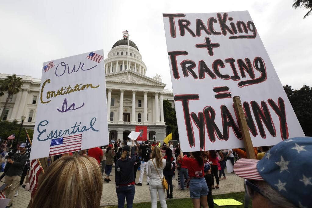 Protesters calling for California Gov. Gavin Newsom to end his stay-at-home orders rally outside the Capitol in Sacramento, Calif., Monday, April 20, 2020. Several hundred people gathered demanding that Newsom ease the restrictions and allow people return to work. (AP Photo/Rich Pedroncelli)