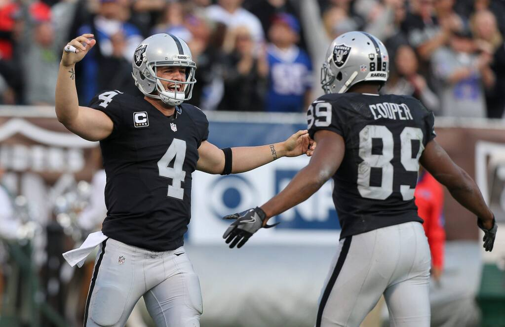 Oakland Raiders quarterback Derek Carr, left, and wide receiver Amari Cooper celebrate connecting for a touchdown in the fourth quarter against the Buffalo Bills in Oakland on Sunday, Dec. 4, 2016. The Raiders defeated the Panthers 38-24. (Christopher Chung / The Press Democrat)