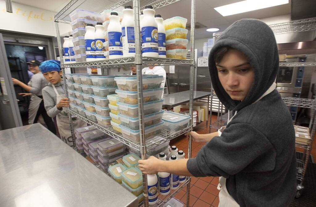 Teen volunteers, wheel out a rack of packaged meals for the low-income ill clients at the Ceres Community Project in Sebastopol. (photo by John Burgess/The Press Democrat)