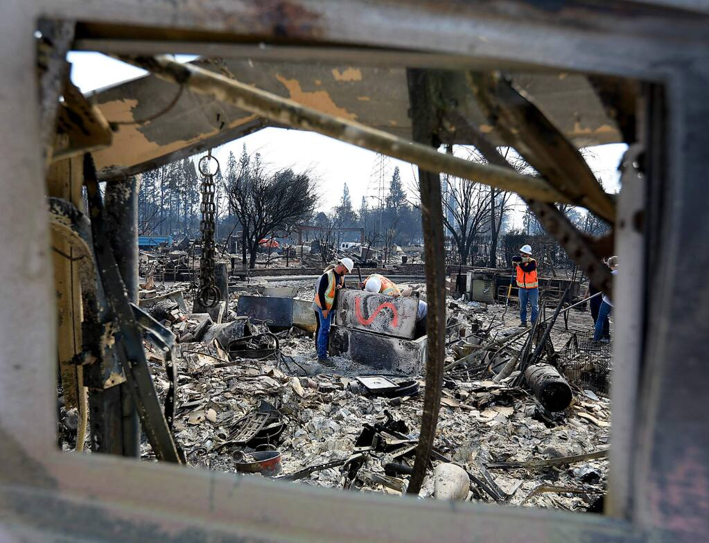 At the Larkfield home of Richard Vignone, his son and a few PG&E workers look to see what was salvageable after the Tubbs fire on Monday, Oct. 16, 2017. (KENT PORTER/ PD)