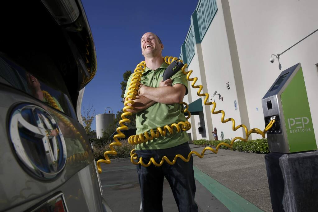 Mark Gmelin, a Materials R&D Engineer and Sustainability Coordinator, stands at one the company's solar powered electric car charging stations for employees at Labcon North America on Wednesday, September 2, 2015 in Petaluma, California . (BETH SCHLANKER/ The Press Democrat)