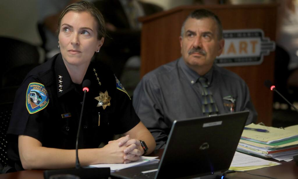 Jennifer McGill, SMART's chief of police, and agency General Manager Farhad Mansourian, watch a video during a SMART board meeting during a presentation about deaths on the SMART tracks. (Kent Porter / The Press Democrat, 2019)