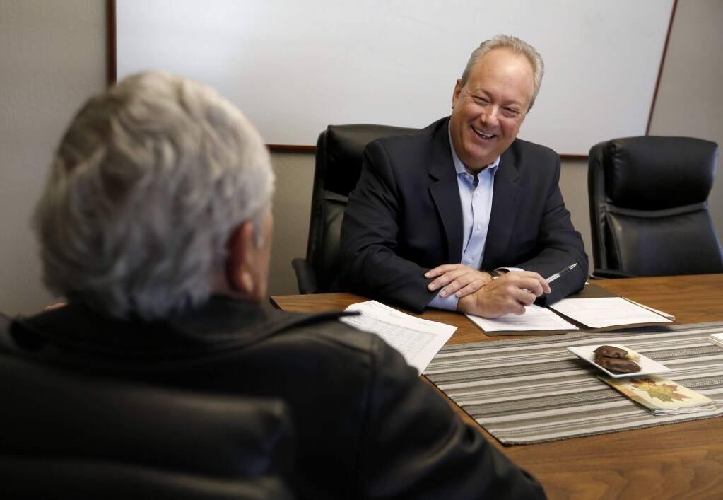 David Brown, right, a certified financial planner and an accredited investment fiduciary, with Encore Wealth Management, goes over a quarterly portfolio report with his client Allen Goldberg at his office in Santa Rosa, on Tuesday, December 6, 2016. (BETH SCHLANKER/ The Press Democrat)