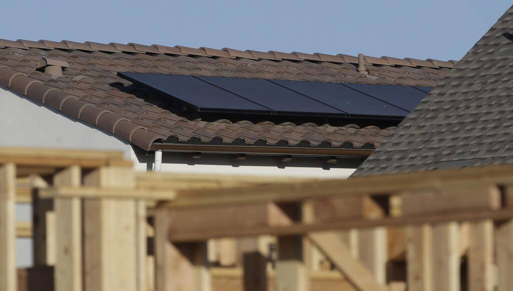 FILE--In this photo file taken Monday, May 7, 2018, solar panels are seen on the rooftop on a home in a new housing project in Sacramento, Calif. (AP Photo/Rich Pedroncelli, file)