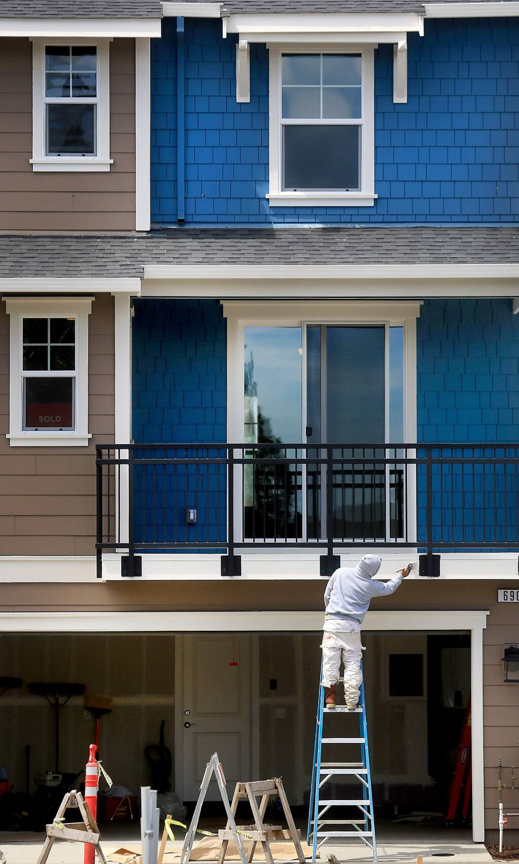 Jaime Martinez Lopez paints trim on a townhouse at Village Walk in Cotati, Thursday April 27, 2017, one of 46 townhomes and single family homes by Synergie Communities. (Kent Porter / The Press Democrat) 2017