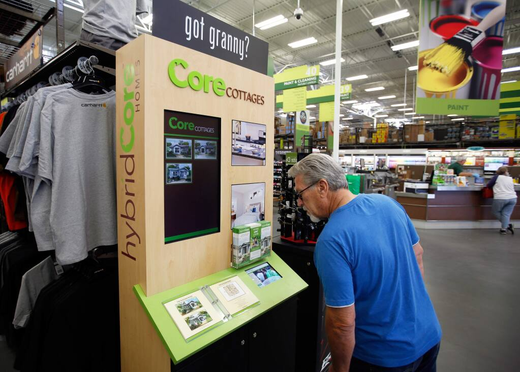 Ron Fuller of Rohnert Park takes a brief look at a hybridCore Homes kiosk showcasing granny unit floor plans and information at Friedman's Home Improvement in Petaluma, California on Sunday, September 24, 2017. (Alvin Jornada / The Press Democrat)