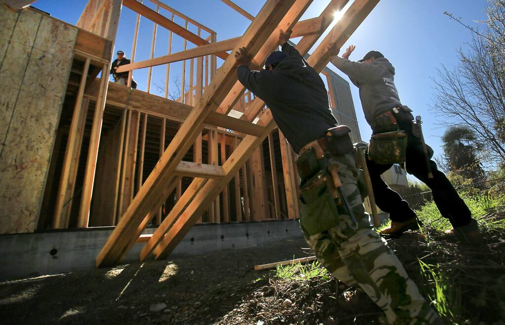 Miguel Gonzalez, left and Raul Rivas combine efforts to lift the framing of an exterior wall as Raul Magana, top left, pulls the structure towards the house, Wednesday March 1, 2017 as the three build a granny unit in Santa Rosa. (Kent Porter / The Press Democrat) 2017