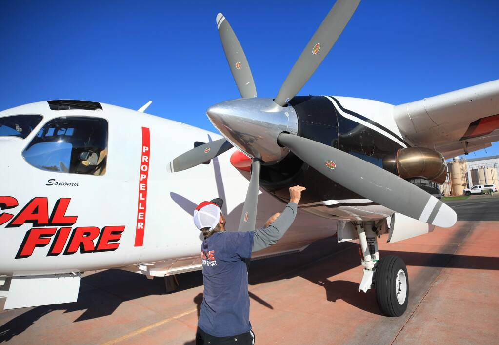 Cal Fire relief Andrew Rhynard turns the prop on an S2-T air tanker to force heat from the engine, Monday, Nov. 25, 2019 at the Sonoma Air Attack Base in Santa Rosa. (Kent Porter / The Press Democrat) 2019