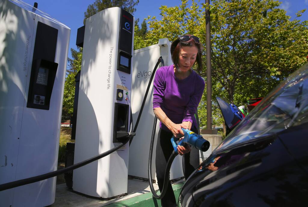 Lorna Ho uncouples her electric vehicle from a charging station in the parking lot of Coddingtown Mall, in Santa Rosa, on Thursday, April 20, 2017. (Christopher Chung/ The Press Democrat)