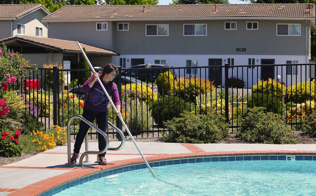 Brookside East Apartments manager Laura Rammer cleans the pool at the apartment complex in Santa Rosa on Monday, May 15, 2017. (Christopher Chung/ The Press Democrat)