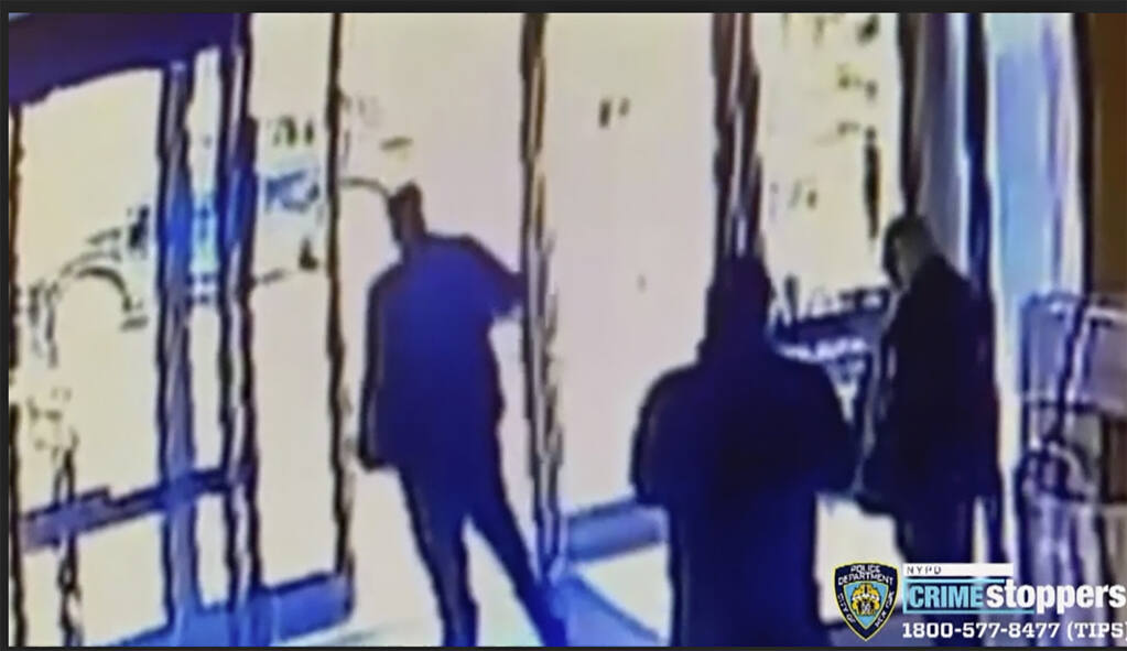 This image taken from surveillance video provided by the New York City Police Department shows an apartment building employee, center, closing the building's front door after a man assaulted a 65-year-old Asian American woman, Monday afternoon, March 29, 2021, a few blocks from New York's Times Square. The property developer and manager of the building wrote on Instagram that it was aware of the assault and said staff members who witnessed it were suspended pending an investigation.(Courtesy of New York Police Department via AP)
