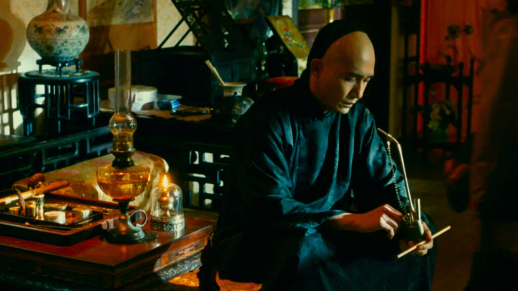 Tony Leung Chiu-wai in 'Flowers of Shanghai' (1998), where ornate doors to the outside world are cracked open, but the women of the flower house never walk through. (High On Films)