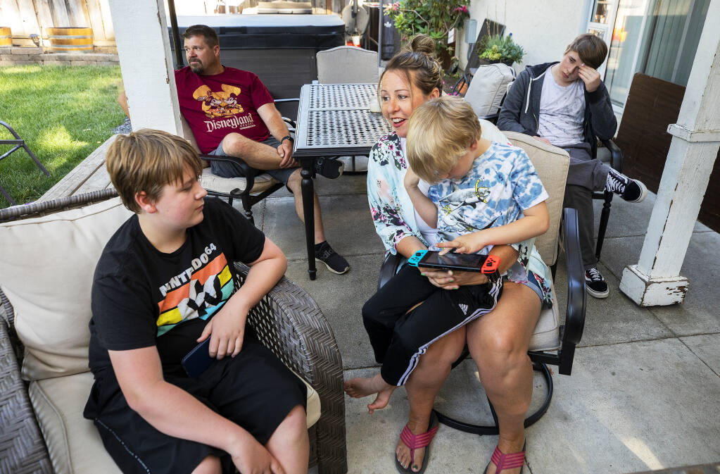 From left, Dylan, 14, dad James, mom Jennifer, Lucas, 6, and Cody, 16, hang out in the backyard of their Windsor home on Monday, May 10, 2021. Mom, dad and Cody have been vaccinated and the family plan to vaccinate Dylan as soon as state approvals for 14-year-olds go into effect. (John Burgess/The Press Democrat)