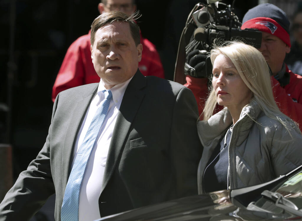 FILE — Investor John Wilson, left, arrives at federal court in Boston with his wife Leslie in this Wednesday, April 3, 2019 file photo, to face charges in a nationwide college admissions bribery scandal. The first trial in the college admissions bribery scandal opened Monday, Sept. 13, 2021, with defense attorneys seeking to portray the two parents accused of buying their kids' way into school as victims of deception who believed their payments were legal donations. (AP Photo/Charles Krupa, File)