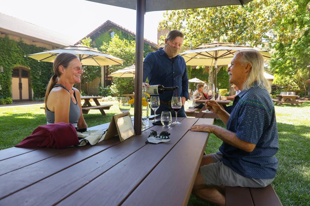 Tasting room manager Ian Eddy, center, pours wine for Amy Kimball, left, Bob Yastishak, visiting from Alameda, at Dry Creek Vineyard near Healdsburg on Thursday, June 3, 2021.  (Christopher Chung/ The Press Democrat)