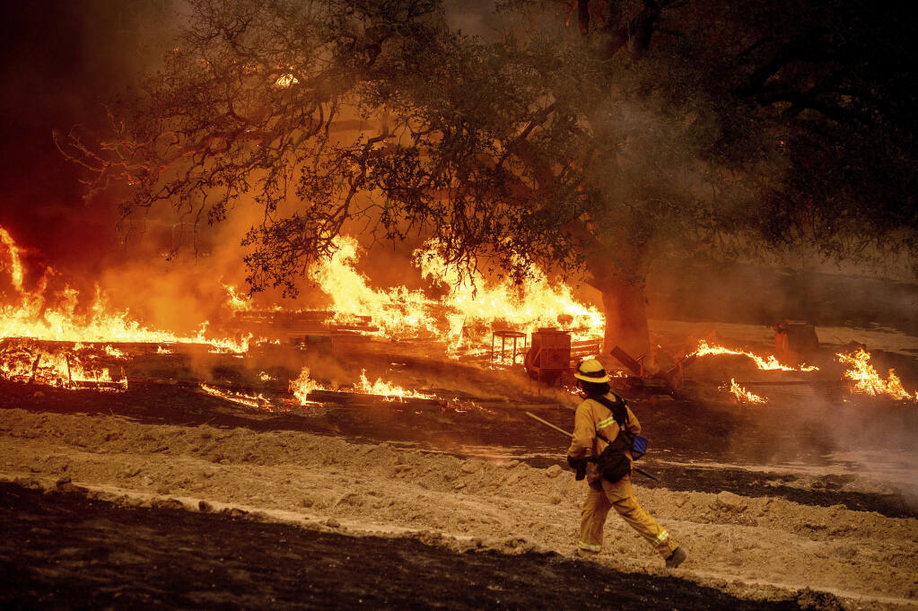FILE - In this Oct. 1, 2020 file photo a firefighter passes flames while battling the Glass fire in a Calistoga, Calif., vineyard.  (AP Photo/Noah Berger, File)