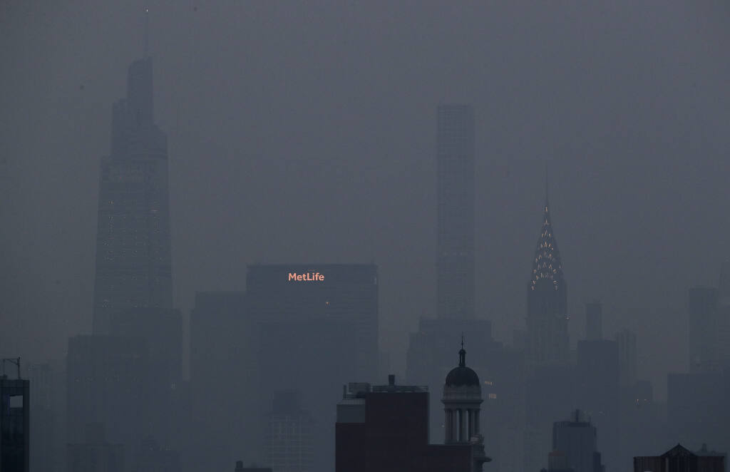 The Met Life and Chrysler buildings glow through a thick haze hanging over Manhattan, Tuesday, July 20, 2021, in New York. Wildfires in the American West, including one burning in Oregon that's currently the largest in the U.S., are creating hazy skies as far away as New York as the massive infernos spew smoke and ash into the air in columns up to six miles high. (AP Photo/Julie Jacobson)