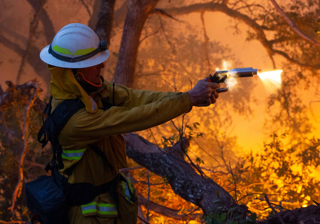 San Bruno Fire battalion chief Bill Forester fires a flare gun down a ravine during a defensive firing operation at Sugarloaf Ridge State Park to create a buffer between the head of the Glass Fire and adjacent communities near Kenwood, California, on Tuesday, September 29, 2020. (Alvin A.H. Jornada / The Press Democrat)